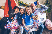 french cheering family sitting on sofa watching soccer match on mobile at home with french flag