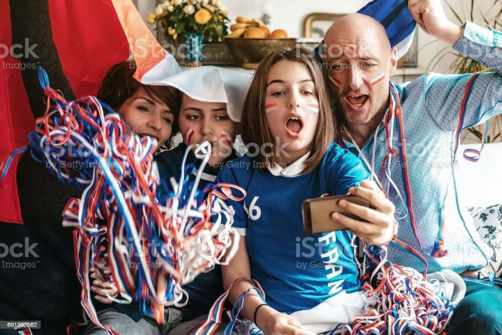 french cheering family watching soccer match on smartphone at home stock photo