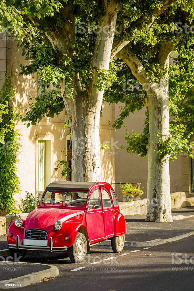 French classic car parked under plane trees stock photo