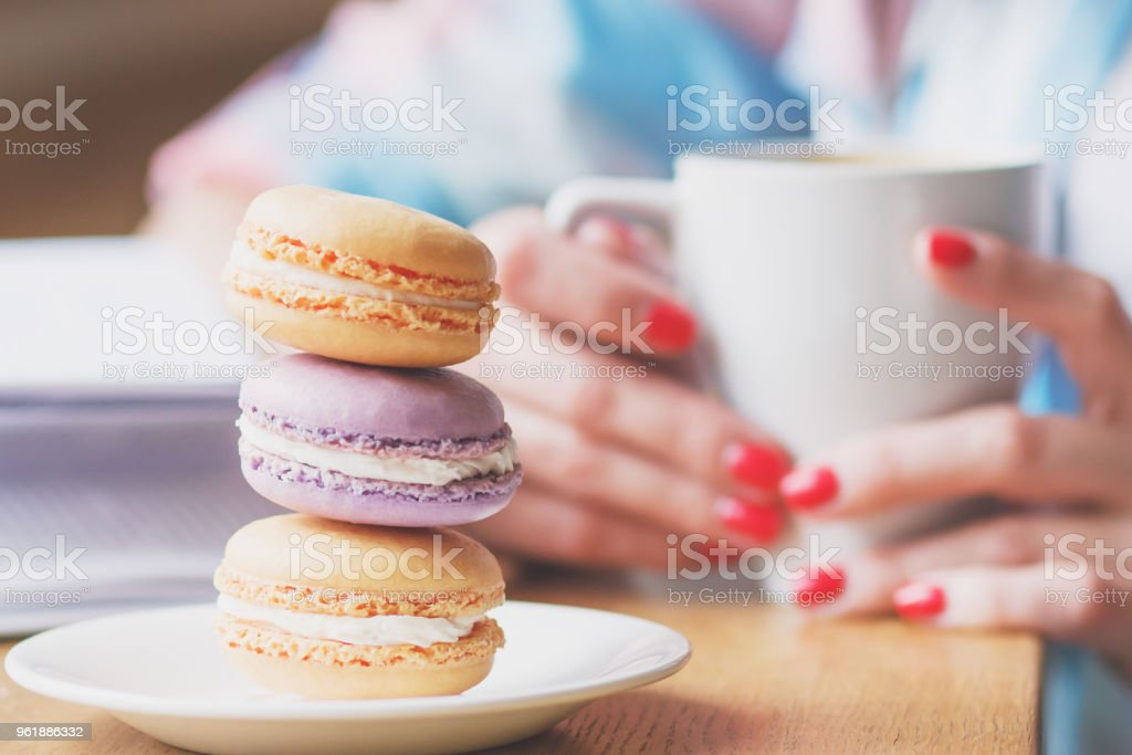 French colored macarons on the plate and a cup of coffee stock photo