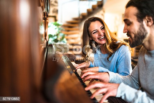istock french couple playing the piano in a parisen house 527910652