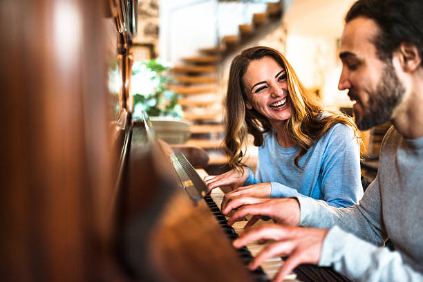 french couple playing the piano in a parisen house french couple playing the piano in a parisen house pianist stock pictures, royalty-free photos & images