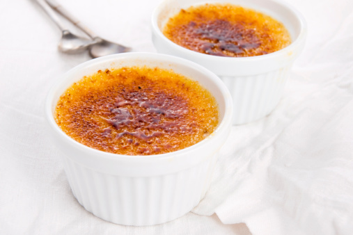 Creme brulee of orange and almond milk and mint on a red background, close up