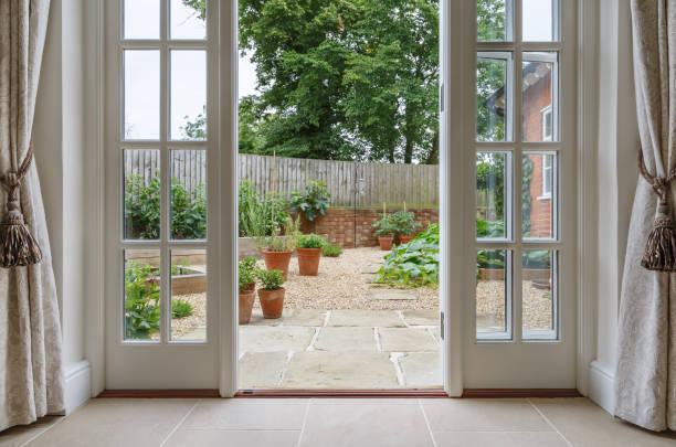 French doors leading to kitchen garden View of garden from inside house with french doors leading to a courtyard kitchen garden doorway stock pictures, royalty-free photos & images