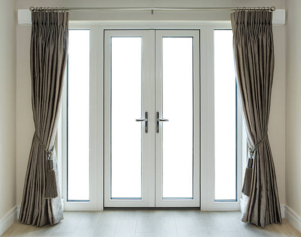 French Doors with Clipping Path a set of white French doors with an elegant set of bronze coloured silk curtains and light caramel coloured walls. The flooring is made from