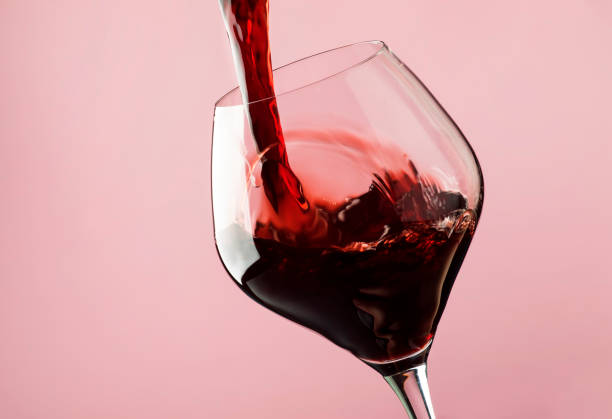 french dry red wine, pours into glass, trendy pink background - versare foto e immagini stock