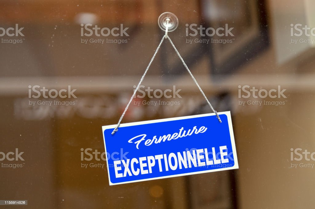 """French exceptional closure sign Blue sign open sign hanging at the glass door of a shop saying in French: """"Fermeture exceptionnelle"""", meaning in English: """"Exceptional closure"""". Bar - Drink Establishment Stock Photo"""