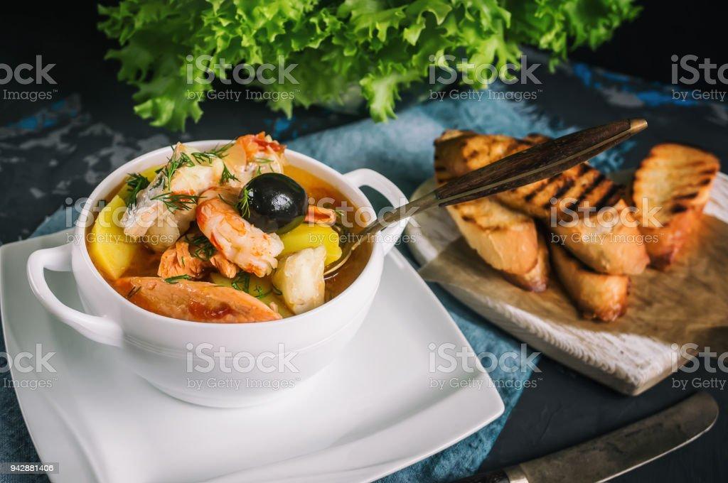 Französische Fischsuppe Bouillabaisse mit Meeresfrüchten, Lachsfilet, Garnelen, reichen Geschmack, köstliches Abendessen in einem schönen weißen Teller – Foto