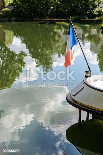 istock French flag dangling with no wind at the stern of a riverboat over still water reflecting a blue and cloudy sky 909630090