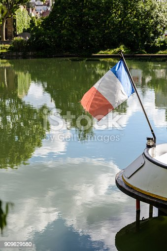 istock French flag flying in the wind at the stern of a riverboat over still water reflecting a blue and cloudy sky 909629580