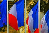 French flags pattern and Euro flag waving against classical facade – Paris, France