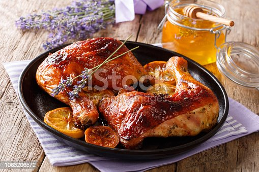istock French food: fried quarters chicken legs with lavender honey, spices and lemon close-up. horizontal 1063206572