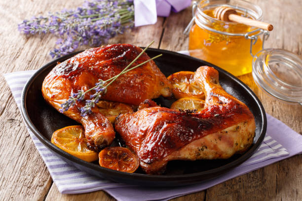 French food: fried quarters chicken legs with lavender honey, spices and lemon close-up. horizontal stock photo