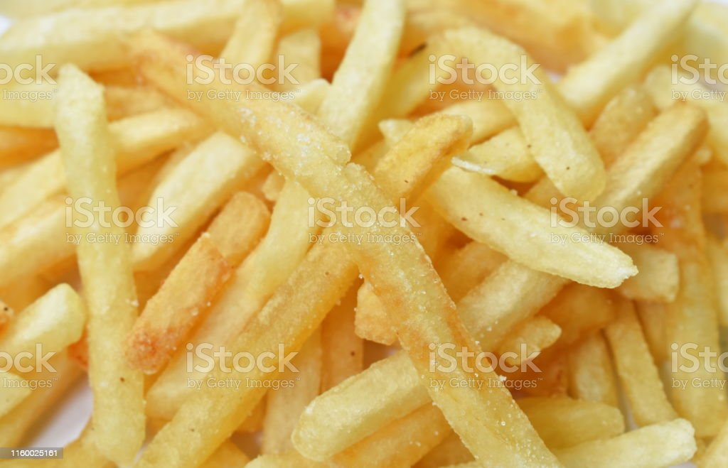 close up of French fried mixed with salt arranging on white background