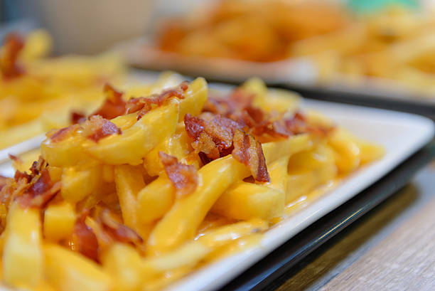 French fries and cheese with bacon on top - foto de stock