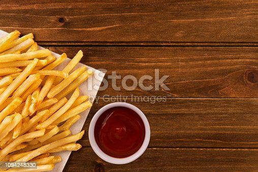 French fries with ketchup on a wooden background, directly above. Close up.