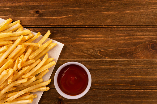 French fries and ketchup on a wooden background