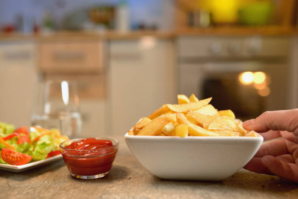 French fries and salad on table in kitchen French fries and salad on table in kitchen patatine fritte stock pictures, royalty-free photos & images