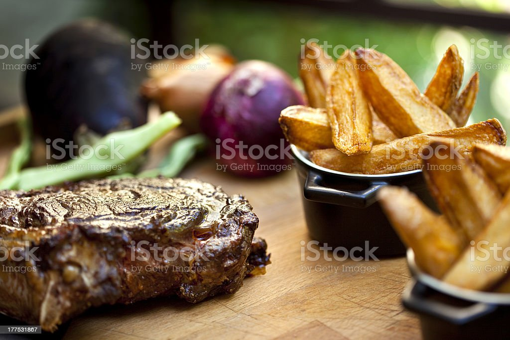French fries and some well done steak on the table  stock photo