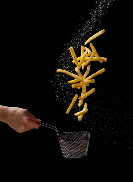 french fries - fried potatoes flying out of basket, fly fastfood - patatine foto e immagini stock
