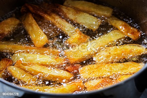 French fries fry in hot bubbling oil in a frying pan