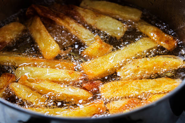 French fries fry in hot bubbling oil stock photo