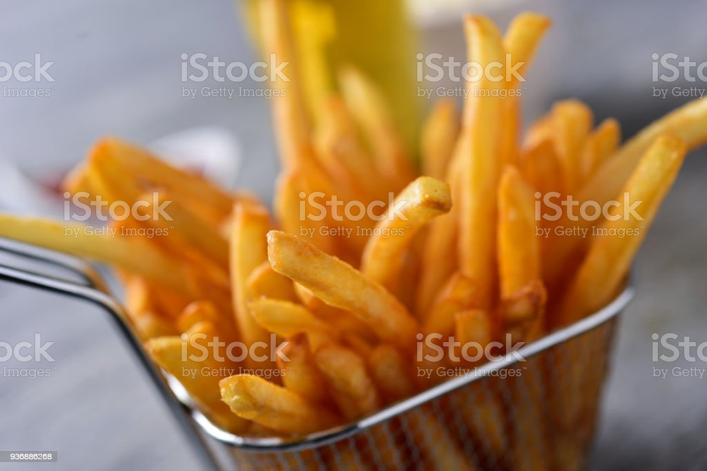 french fries in a metal basket stock photo