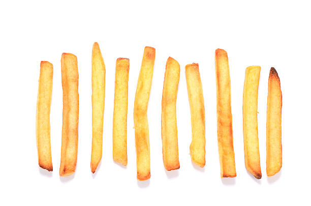 french fries in a row on white background - friet stockfoto's en -beelden