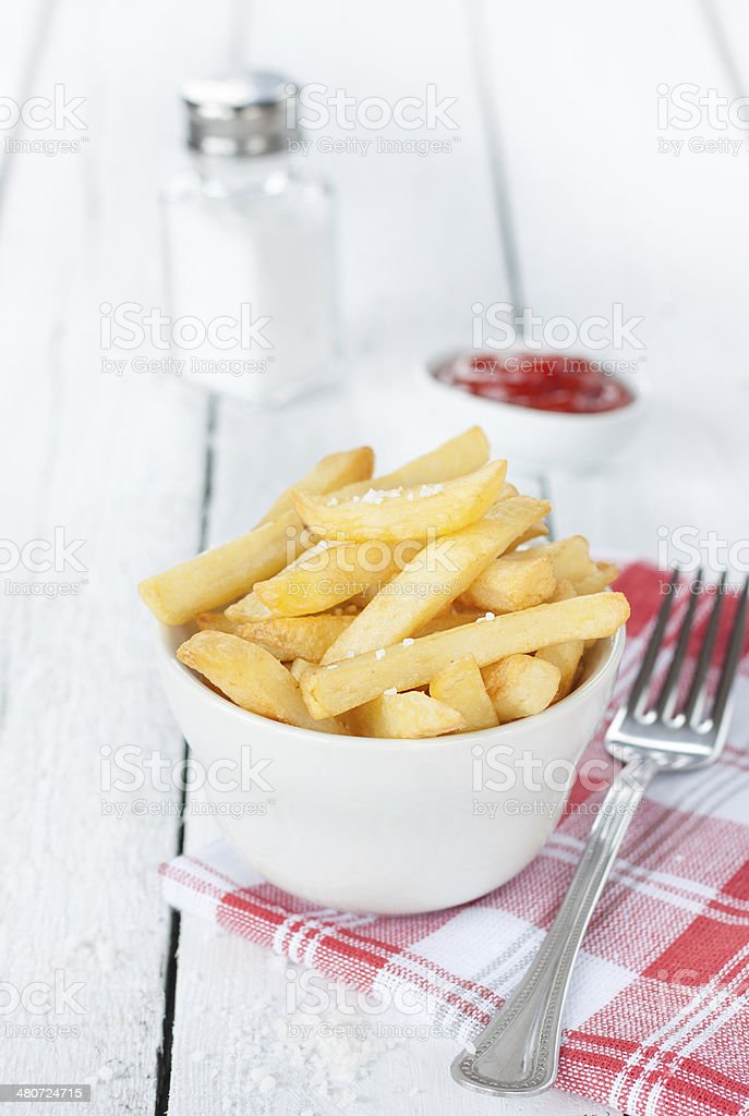French fries in a white bowl on table stock photo