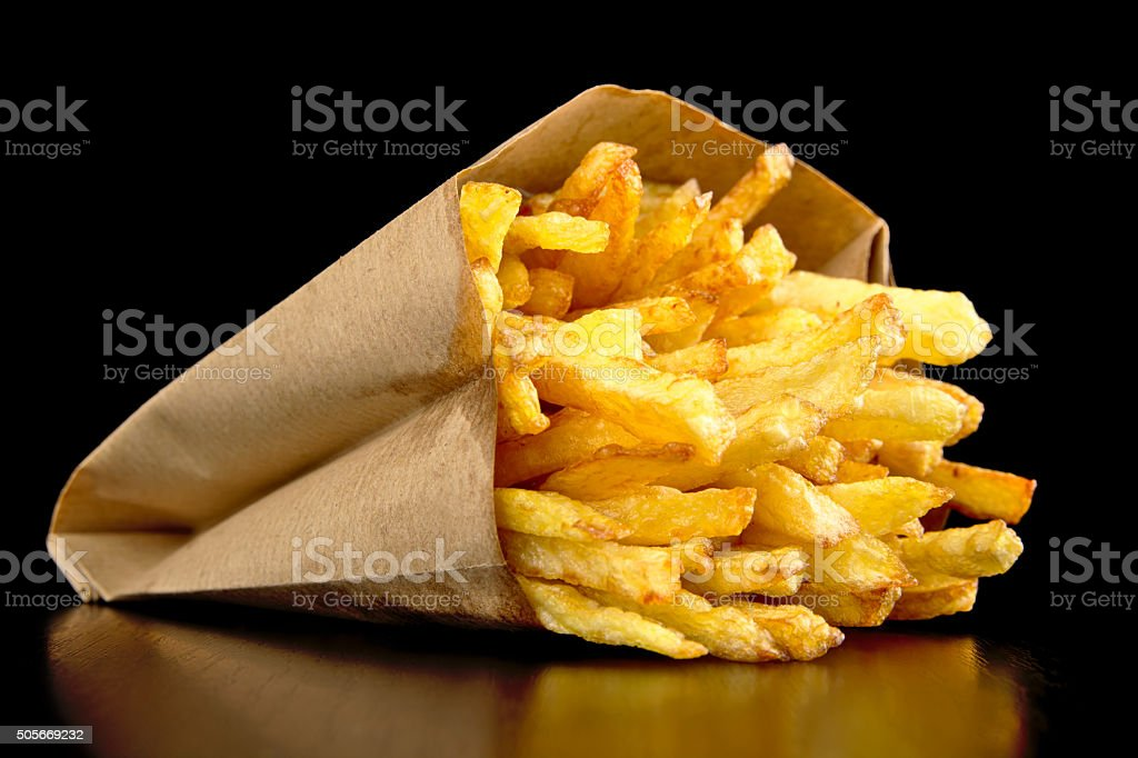 French fries in the paper bag isolated on black stock photo