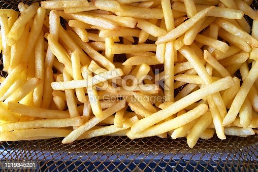 Strips of potato chips piled into the basket of an electric fryer. Golden potato texture. Useful in work related to cooking and recipe preparation, or topics of healthy eating, calories and carbohydrates.