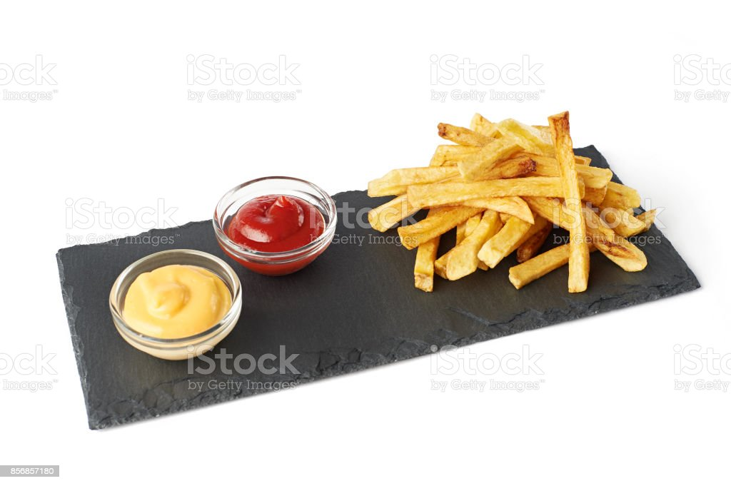 French fries on black cutting board with ketchup and cheese sauce isolated on white stock photo