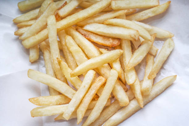 French fries on white blotting paper oil French fries on white blotting paper oil blotting paper stock pictures, royalty-free photos & images