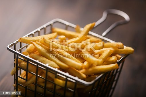 French Fries in a metal basket on a wooden background.