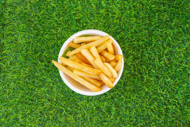 French fries French fries yellow on green grass, top view close up. fried potato stock pictures, royalty-free photos & images