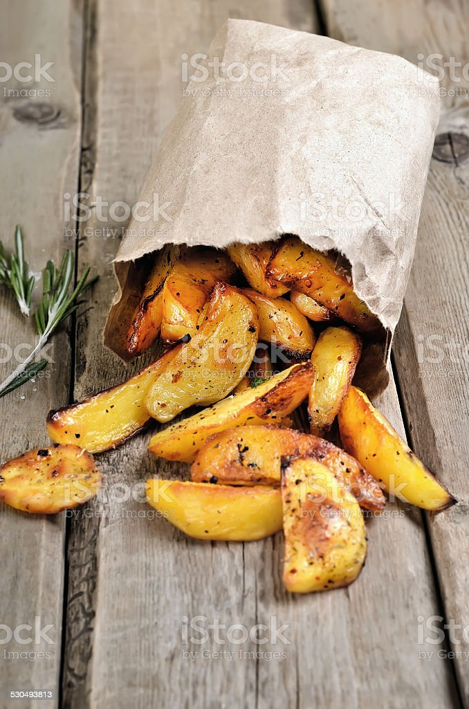 French fries potato wedges in paper bag stock photo