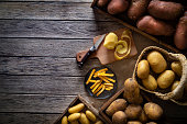 French fries potatoes on a rustic wooden board table with raw potatoes around of different colors and sizes shapes