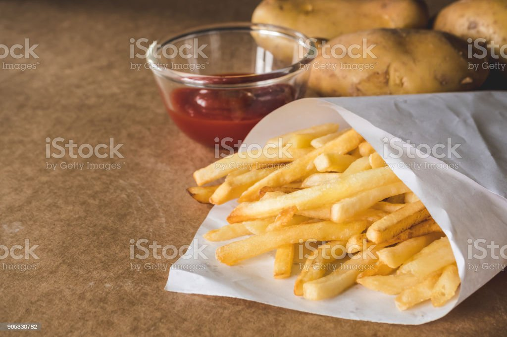 French fries with ketchup and raw potatoes on wooden table. royalty-free stock photo