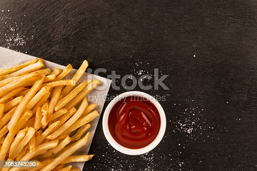 French fries with ketchup on dark background, directly above. Close up.