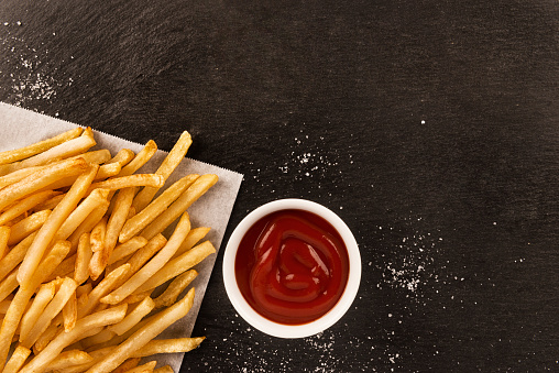 French fries with ketchup on dark background, directly above.
