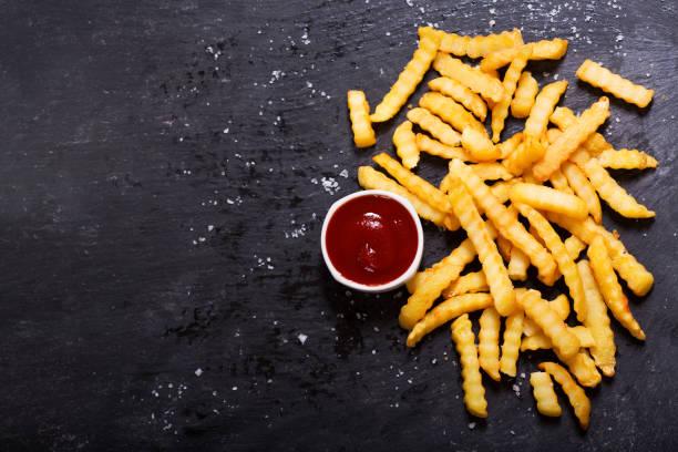 frites met ketchup op donkere tafel - patat stockfoto's en -beelden