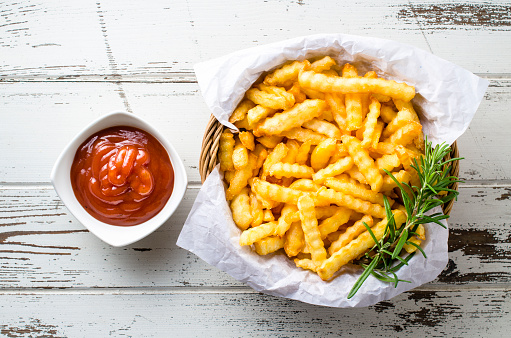 French fries with ketchup over old wooden table