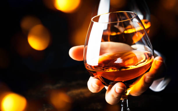 French glowing cognac glass in hand on the dark bar counter background, copy space, selective focus French glowing cognac glass in hand on the dark bar counter background, copy space, selective focus calvados stock pictures, royalty-free photos & images