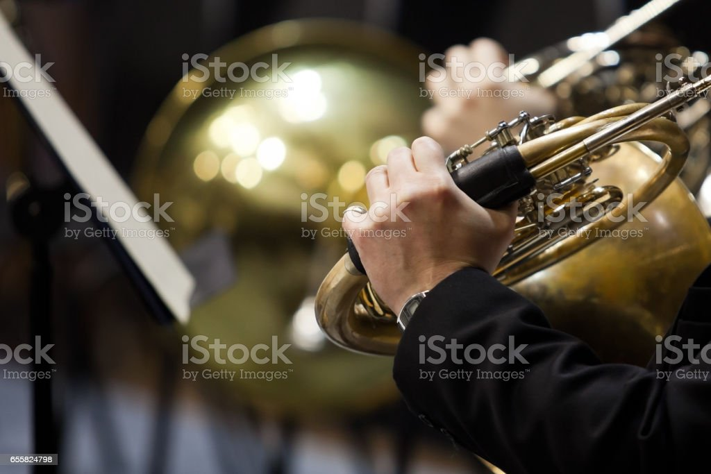 French horn in the hands of a musician stock photo