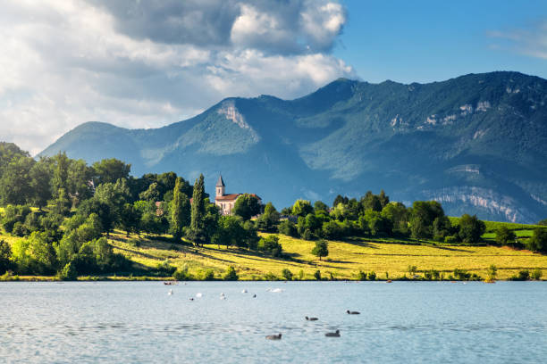 französische landschaft mit kleinen kirchturm entlang der rhône und der grand colombier bugey alpen berge im sommer in auvergne-rhone-alpes - kirchturmspitze stock-fotos und bilder