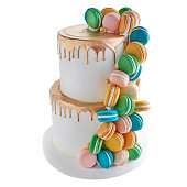 A decorated tiered cake decorated with cascading French macarons.