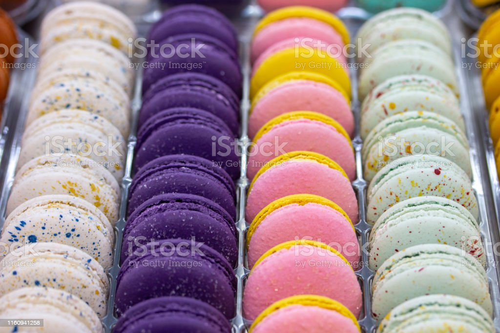 French macaroons are arranged in smooth rows of white pink purple....