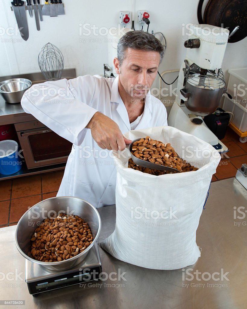 French male craftsman weighting fresh almonds for sweet nougat specialty stock photo