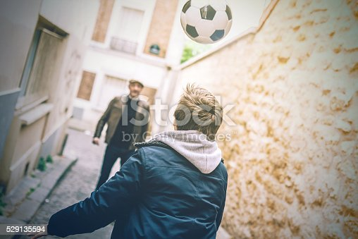 french man playing soccer with son in Paris street