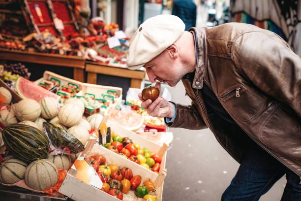 französischer mann riechen auf tomaten in garküche in paris - bio lebensmittel stock-fotos und bilder